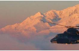helicopter flying across the Alps